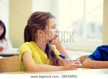 education, elementary school, learning and people concept - school girl with pen being bored in classroom