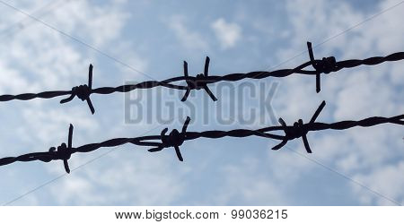 Two Barbed Wire Silhouette With Blue Sky Background.