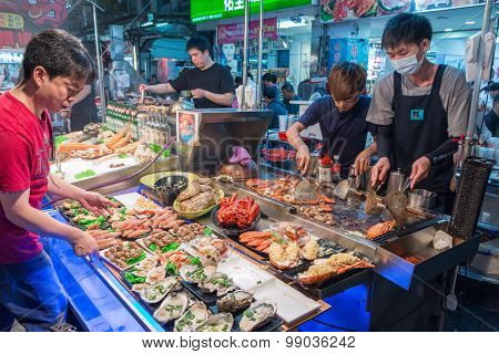 KAOHSIUNG TAIWAN - APR 20 : Chief prepares seafood to be sold in Kaohsiung night market on April 20 2015. People enjoy food at night market in Taiwan. And is one of the unique culture in Taiwan.