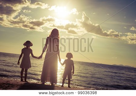 Mother And Children Standing On The Beach At The Sunset Time.
