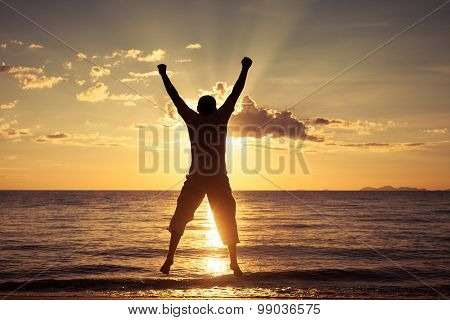 Man Jumping On The Beach At The Sunset Time