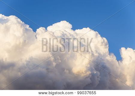 Part Of A Large Cumulus Clouds Illuminated By The Sun On A Background Of A Piece Of Clear Blue Sky