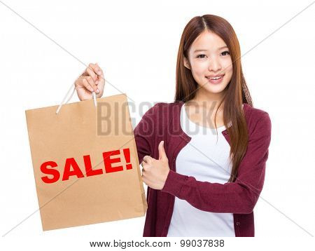 Young Woman hold with shopping bag and thumb up for showing a word sale!