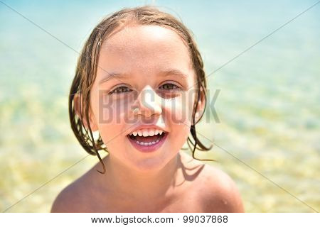 Girl On The Beach Is Smiling And Looking At The Camera.
