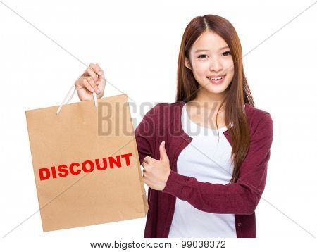 Young Woman hold with shopping bag and thumb up for showing a word discount