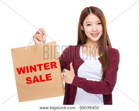 Young Woman hold with shopping bag and thumb up for showing winter sale