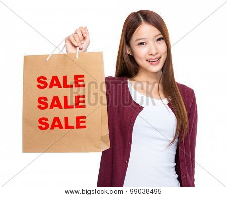 Asian woman take shopping bag and showing three sale word