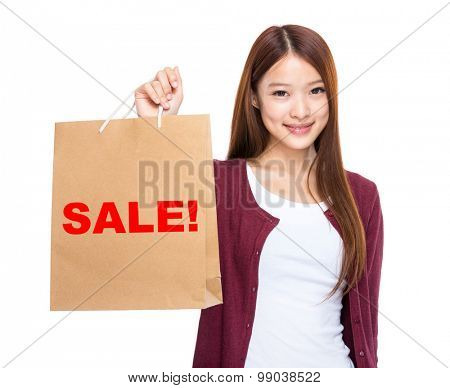 Woman hold with shopping bag and showing a word sale!