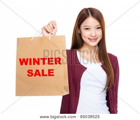 Woman hold with shopping bag and showing winter sale