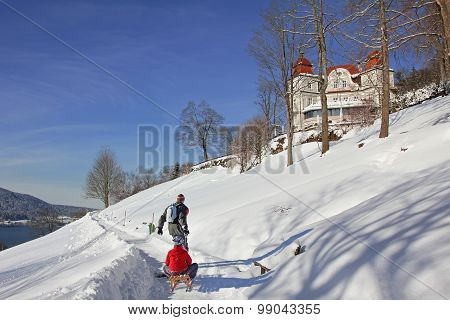 Father Pulling Son With A Sledge, Winter Hiking Trail, Tegernsee