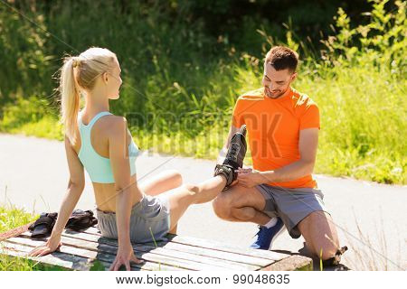 fitness, sport, summer, couple and healthy lifestyle concept - happy man helping woman to put on roller skates outdoors