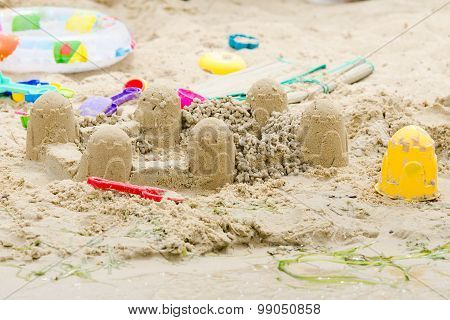Sand Castle Circle And Toys On The River Bank