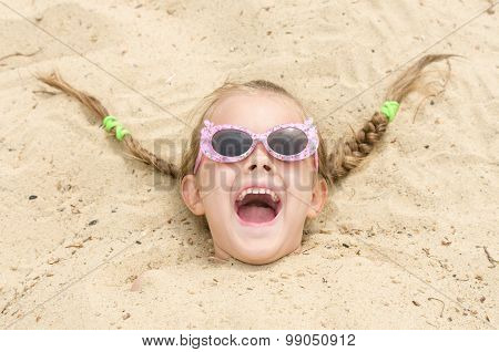 Five-year Girl With Glasses On A Beach Strewn On His Head In The Sand