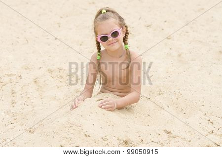 Five-year Girl With Glasses On Beach Covered With Sand Up To His Waist