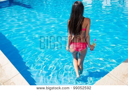 Back view portrait of a woman standing in swimming pool
