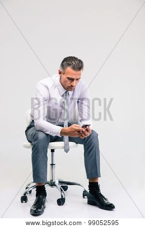 Portrait of a handsome businessman sitting on the office chair and using smartphone isolated on a white background
