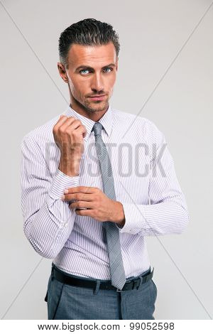 Handsome businessman buttoning cuff sleeves isolated on a white background