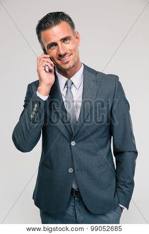 Portrait of a happy businessman talking on the phone isolated on a white background