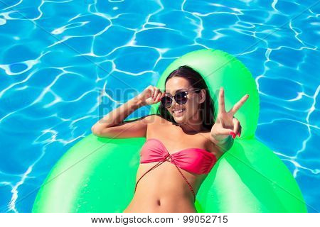 Portrait of a smiling girl lying on air matress and showing victory sign in swimming pool