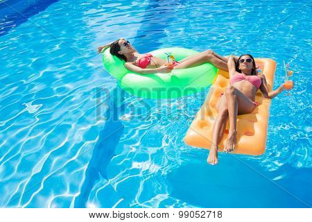 Two beautiful girls resting on air mattress in swimming pool with cocktails