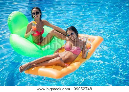 Portrait of a two girls lying on air mattress in swimming pool and holding cocktails