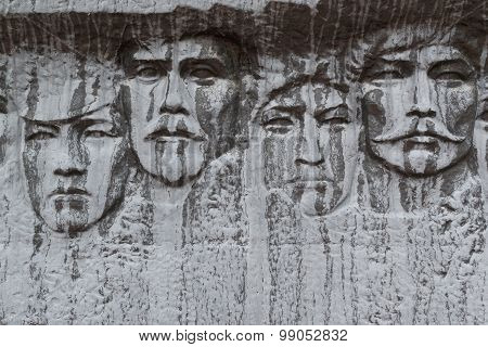 Human Faces Carved In Black Stone