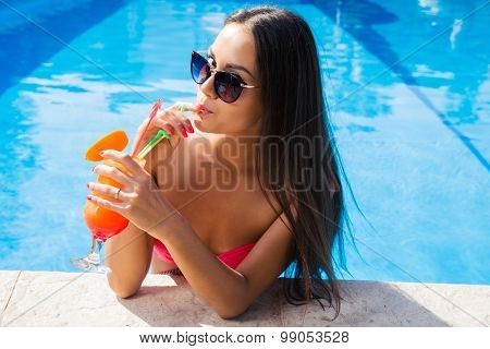 Portrait attractive woman in swim pool drinking cocktail outdoors