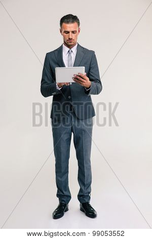 Full length portrait of a confident businessman using tablet computer isolated on a white background