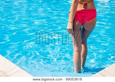 Back view portrait of a young woman standing in swimming pool