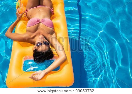 Young girl sunbathing on air mattress in the swimming pool