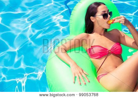 Portrait of attractive woman lying on air mattress and eating orange in swimming pool
