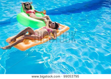 Two happy girls holding cocktails and lying on air mattress in swimming pool