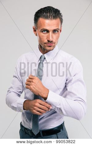 Confident businessman buttoning cuff sleeves isolated on a white background
