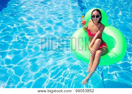 Portrait of a beautiful woman resting on air mattress in swimming pool