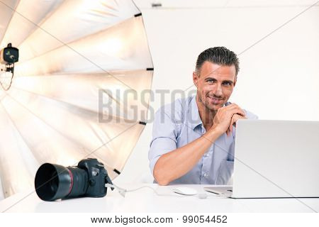 Portrait of a smiling photographer using laptop at his workplace and looking at camera