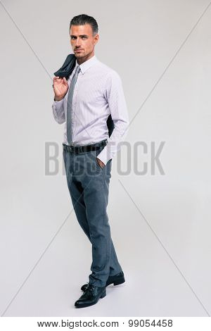 Full length portrait of a handsome businessman standing with jacket on shoulder isolated on a white background