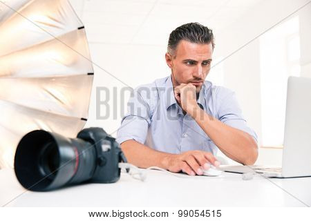 Portrait of a handsome photographer using laptop at his workplace