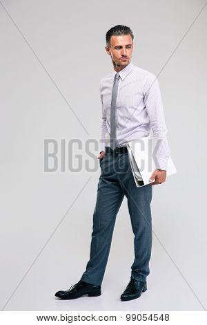 Full length portrait of a handsome businessman standing with folder isolated on a white background