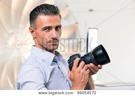 Portrait of a handsome photographer holding camera and looking at camera
