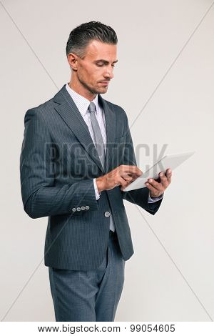 Portrait of a handsome businessman using tablet computer isolated on a white background