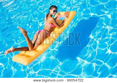 Portrait of attractive woman lying on air mattress in the swimming pool