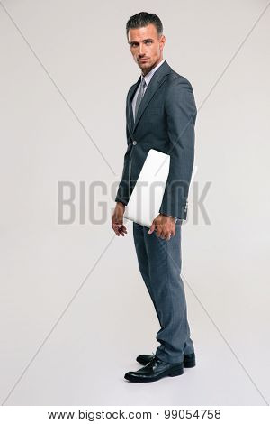 Full length portrait of a handsome businessman standing with laptop and looking at camera over gray background