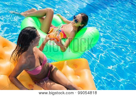 Portrait of a two girlfriends sunbathing on air mattress and drinking cocktails in swimming pool