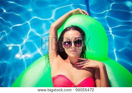 Beautiful woman in sunglasses lying on air mattress in the swimming pool