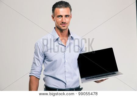 Portrait of a happy businessman showing blank laptop computer screen isolated on a white background