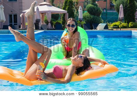 Two funny girls lying on air mattress in swimming pool with cocktails