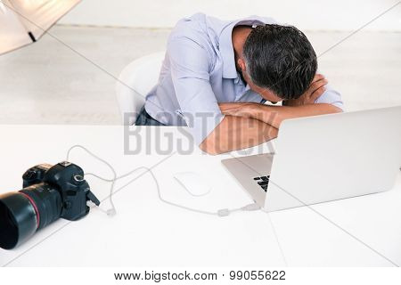 Photographer sleeping at his workplace in studio