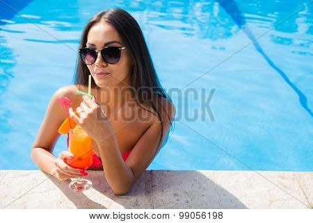 Portrait of a charming woman standing in swim pool and drinking cocktail