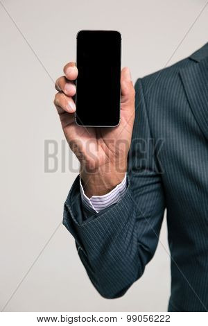 Closeup portrait of a businessman showing blank smartphone screen isolated on a white background
