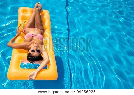 Attractive girl resting on air mattress in the swimming pool